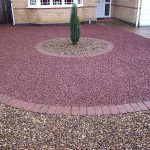 A clean - sharpe, tidy front garden using tweed pebbles and red granite chippings.